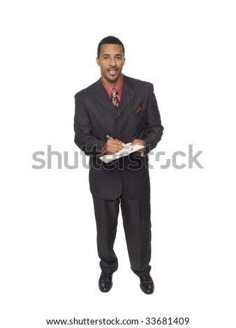 Isloated full length studio shot of an African American man looking at the camera while smiling and writing on a clipboard he is holding.