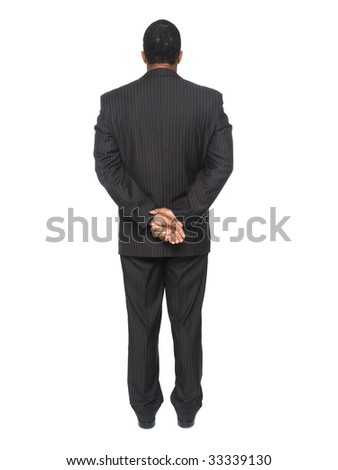 Isloated full length studio shot of an African American man looking away from the camera while clasping his hands. - stock photo