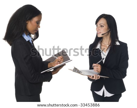 Isloated studio shot of an African American and Caucasian businesswomen writing on their notepad and clipboard. - stock photo