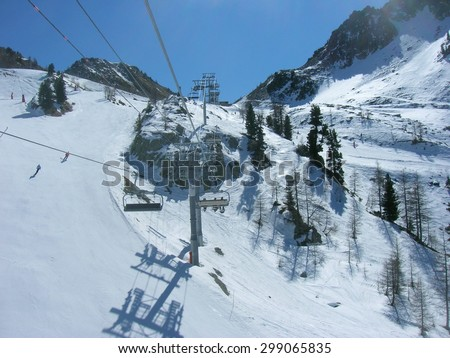 ISOLA, FRANCE - MARCH 26, 2012: Ski runs and a chair lift in ISOLA 2000, a French ski resort in the southern French Alps, located about 90 km from Nice, on a sunny day. - stock photo