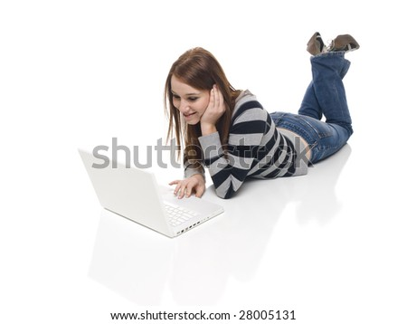 Isolate studio shot of a casually dressed, happy young adult woman working on a laptop computer while laying down. - stock photo