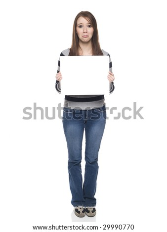Isolate studio shot of a casually dressed young adult woman holding a blank sign with a sad expression on her face. - stock photo