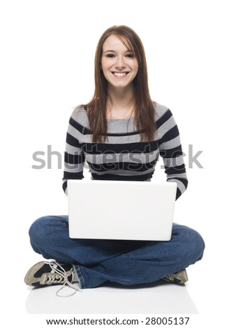 Isolate studio shot of a casually dressed young adult woman sitting and working on a laptop computer. - stock photo