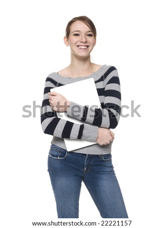 Isolate studio shot of a casually dressed young adult woman smiling as she holds her laptop computer to her chest. - stock photo