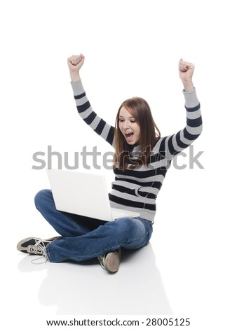 Isolate studio shot of a casually dressed young adult woman staring at her laptop in surprise and celebrating. - stock photo