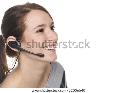 Isolate studio shot of a casually dressed young adult woman wearing a telephone headset and smiling. - stock photo