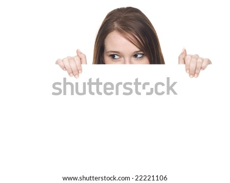 Isolate studio shot of a young adult woman peeking over the edge of a blank sign and looking to the left. - stock photo