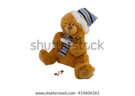 isolate the macro children's toy teddy bear in a scarf with tablets takes temperature a electronic thermometer - stock photo