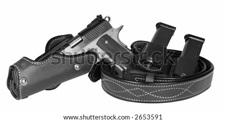 Isolated automatic pistol with belt, holster, and magazines - stock photo