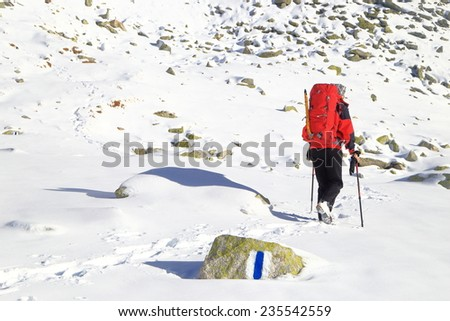 Isolated backpacker traversing a snow covered trail on the mountain - stock photo