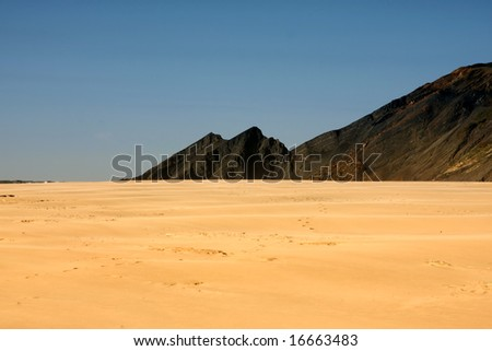Isolated beach with footprints and cliffs on diagonal