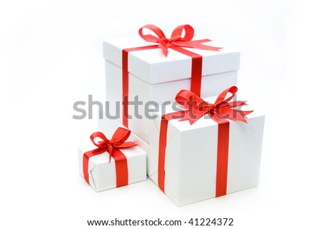 Isolated beautiful white gifts are tied up by a red tape - stock photo