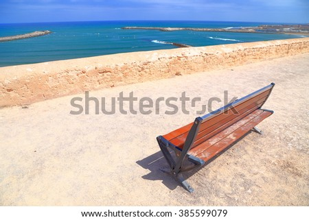 Isolated bench on sunny terrace with the Bou Regreg river and Atlantic ocean in the background, Kasbah of the Udayas, Rabat, Morocco - stock photo