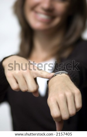 Isolated black amd white female model pointing to her watch