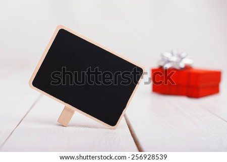 Isolated black chalk board on a white background with a red gift on background. Greeting Card. 8 march. Mothers day. Happy womens day - stock photo