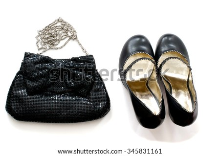 Isolated black clutch bag with high heels shoes over white - stock photo
