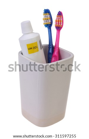 isolated blue and pink toothbrushes in the glass - stock photo