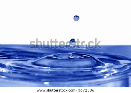 isolated blue drops are falling down and impact with liquid surface - stock photo