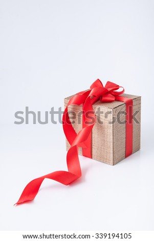 Isolated brown cardboard gift box with red ribbon and bow on white background