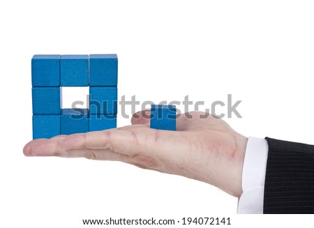 Isolated building blocks with human hand on white background - stock photo