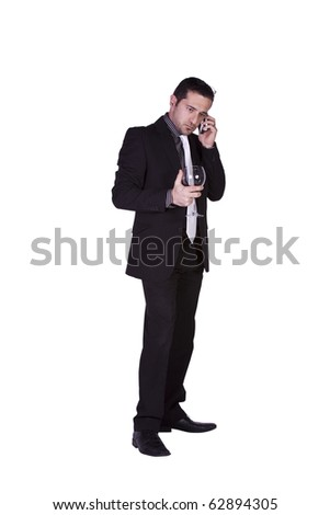 Isolated businessman celebrating with a glass of drink while talking on the phone - stock photo