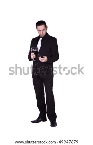Isolated businessman celebrating with a glass of drink while texting on his cell phone
