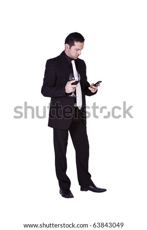 Isolated businessman celebrating with a glass of drink while texting on his cell phone - stock photo