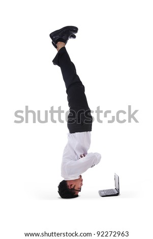 Isolated businessman headstand with laptop on white background - stock photo