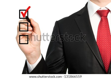 Isolated businessman in a suit with a red tie holding a pen and writing red check mark or make a choice - stock photo