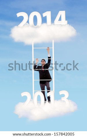 Isolated businessman trying to climb upward on white background