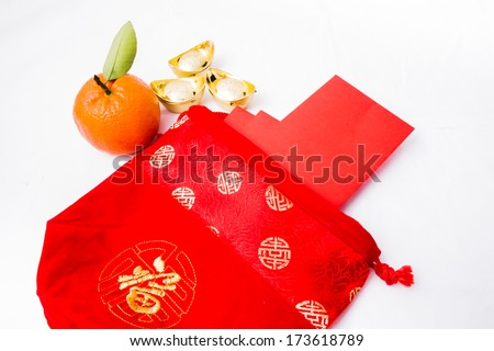 Isolated Chinese new year decoration, Chinese red pockets in red bag, ancient Chinese golden ingots and mandarin orange - stock photo