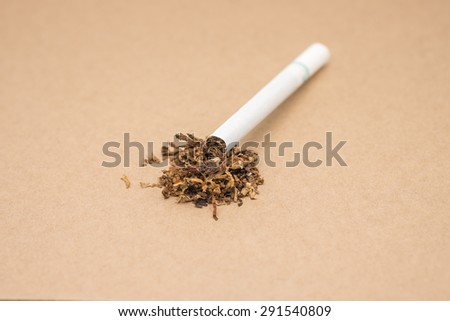 Isolated cigarette butt with tobacco on brown background - stock photo
