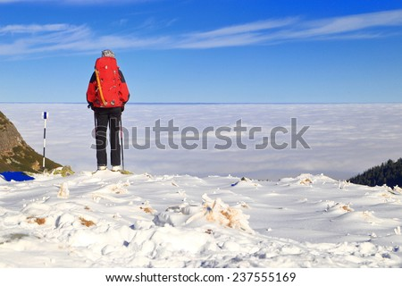 Isolated climber on a snowy trail above clouds - stock photo