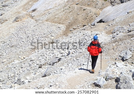 Isolated climber walking on sunny trail surrounded by a rock field, Catinaccio massif, Dolomite Alps, Italy - stock photo
