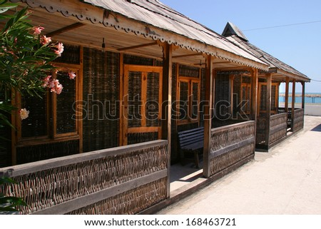 isolated close-up exterior of twigs braided house with a veranda and a wooden roof on a sunny summer day