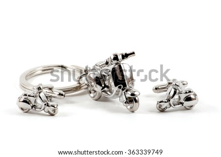 Isolated close up of keychain motorbike and cufflinks over white - stock photo