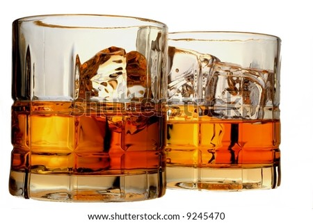 Isolated close-up of liquor and ice in glasses. - stock photo