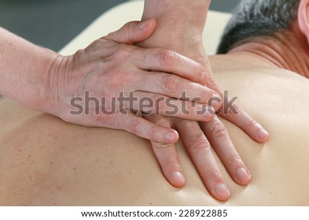 Isolated close-up of the hands of the masseur - female on man's back during a session, studio