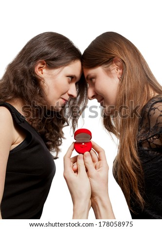 Isolated closeup portrait of two women rivals conflicting because of ring being held by man - stock photo