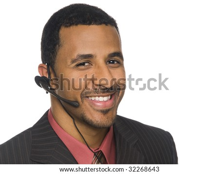 Isolated closeup studio shot of an African American businessman smiling while talking on a telephone headset and looking at the camera. - stock photo