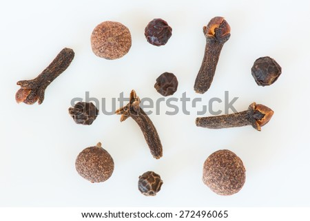 Isolated cloves, allspice and black peppers still life - stock photo