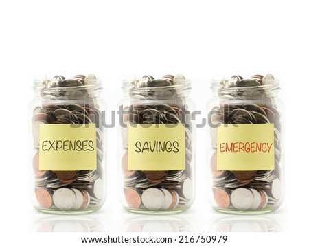 Isolated coins in jar with expenses, savings and emergency label. - stock photo