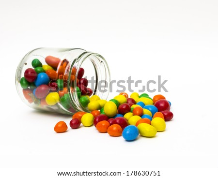 Isolated colorful candy out of jar on white background  - selective focus