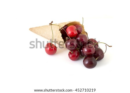 Isolated cornet with fresh cherries on white background