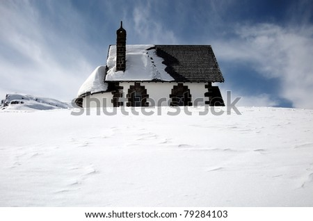 Isolated cottage in snow covered landscape - stock photo