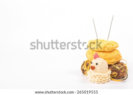 isolated crochet toy chicken on a background of skeins - stock photo