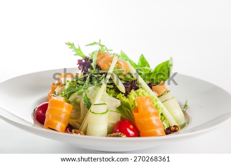 Isolated Delicios Salad with salmon, mix lettuce, arugula, cucumber, walnuts, cherry tomatoes garnished with a sprig of basil on a white plate - stock photo