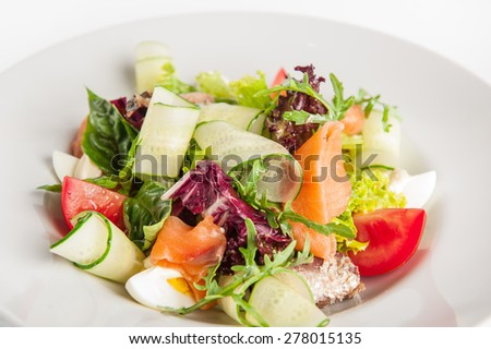 Isolated Delicious Salad with grilled and fresh salmon, mix lettuce, arugula, cucumber, tomatoes and eggs garnished with a sprig of basil on a white plate  - stock photo