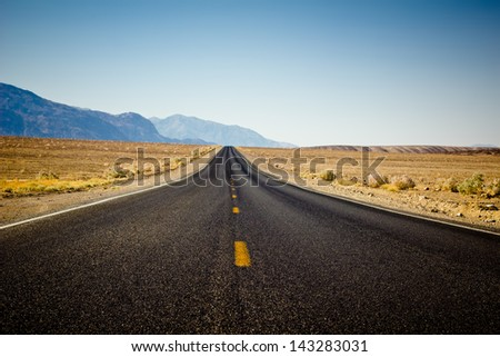 Isolated desert road through Death Valley - stock photo