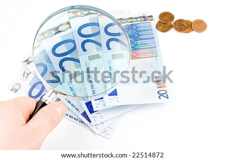 Isolated euro money under the reading glass kept in hand - stock photo